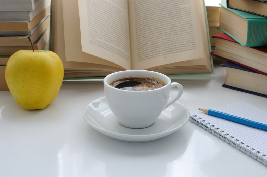 A cup of coffee and an apple on a table of books with a notebook and pencil